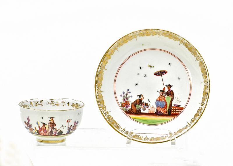 Tea Bowl and Saucer with Chinoiserien. Meissen. Circa 1730-35. Porcelain, enriched in colours and in gilt. Tea bowl with two rust-red rings, above which runs a band of figural scenes upon a grass base. The inner edge contains a gold lace border and the ground a purple scene of Chinese figures. Saucer with corresponding gold border and two rust-red rings around the center, framing a scene with three Chinese figures. Verso with indian flowers. Height 4,5cm/ + 13,5cm.