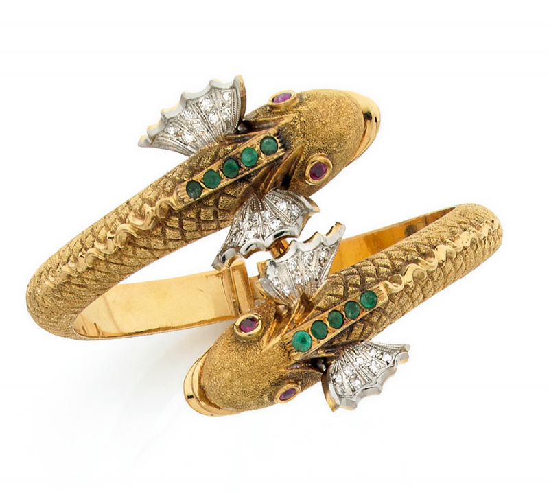 Hinged bangle, decorated with two stylized dolphins heads punctuated emeralds, rubies and diamonds, finely chiseled body.  Around 1950.