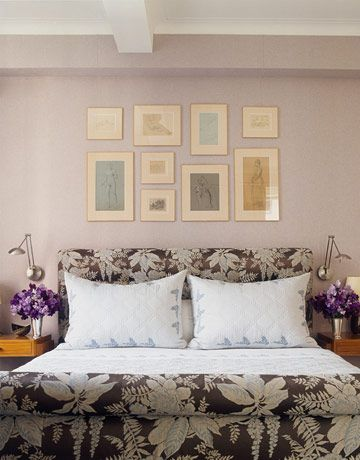 """""""Hanging pictures is an art — and a lot of measuring,"""" says Kleinberg, who arranged these drawings to form a larger rectangle. The bed is upholstered in Nancy Corzine's Orlean. Bedding by Chaz Stevens."""