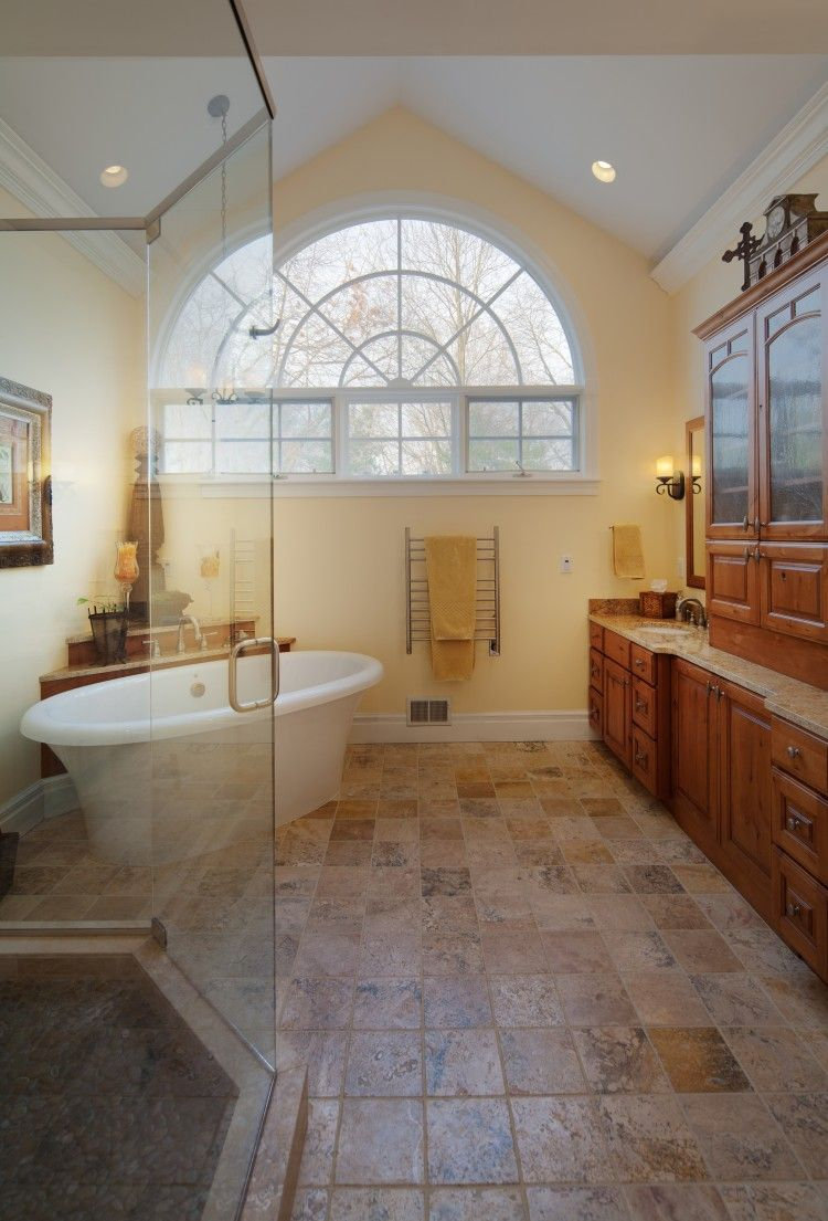 Sun-filled #bathroom with a large natural limestone shower and a ...