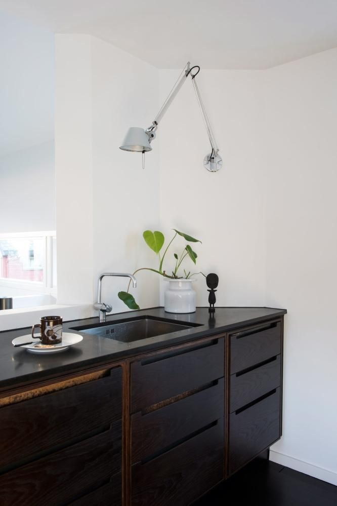 dark wood lower cabinets + white + swing-arm sconce