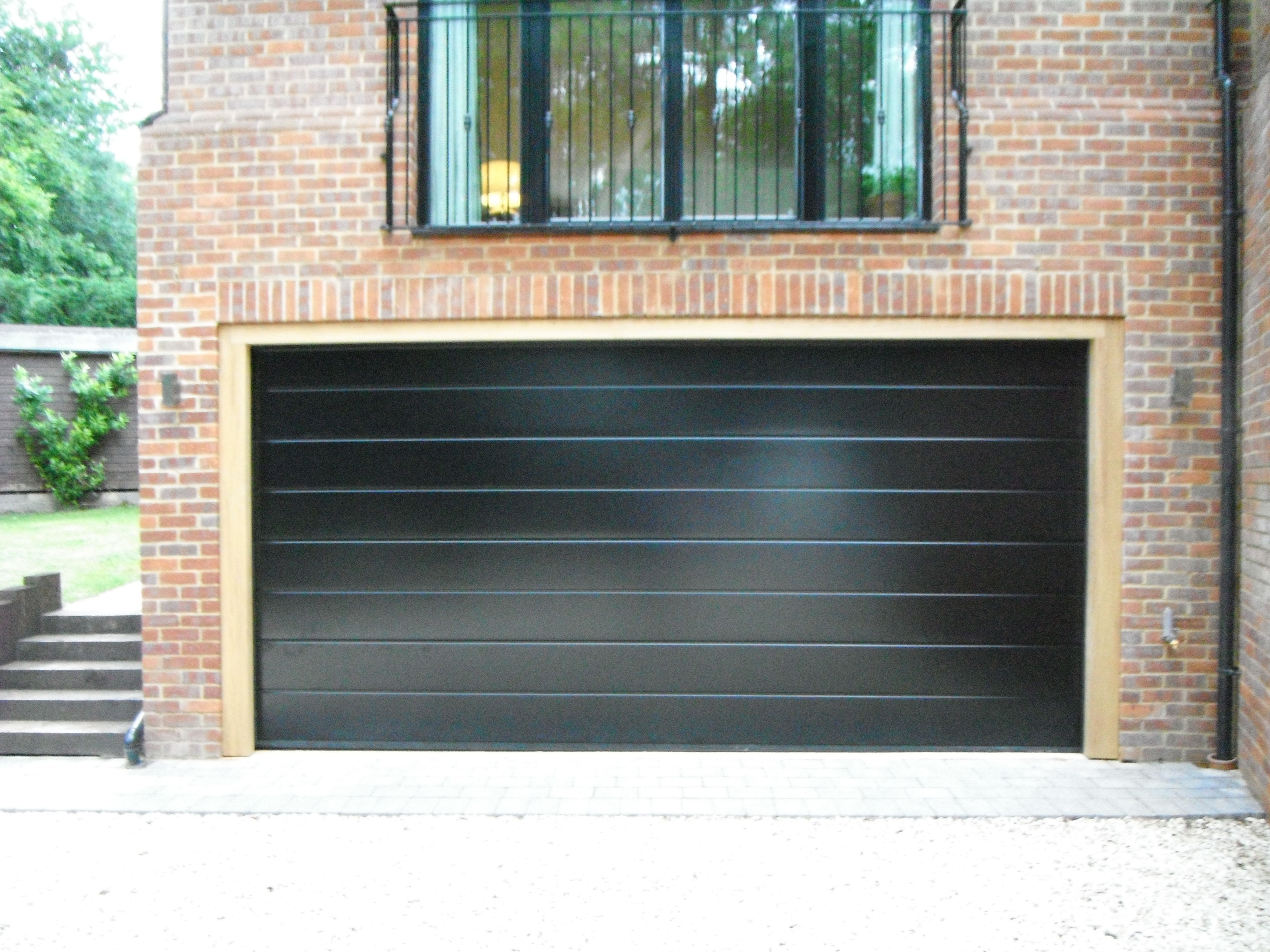 Doors and sidelights matching window on front and black onduline roof - Hormann Sectional M Ribbed In Black Garage Door