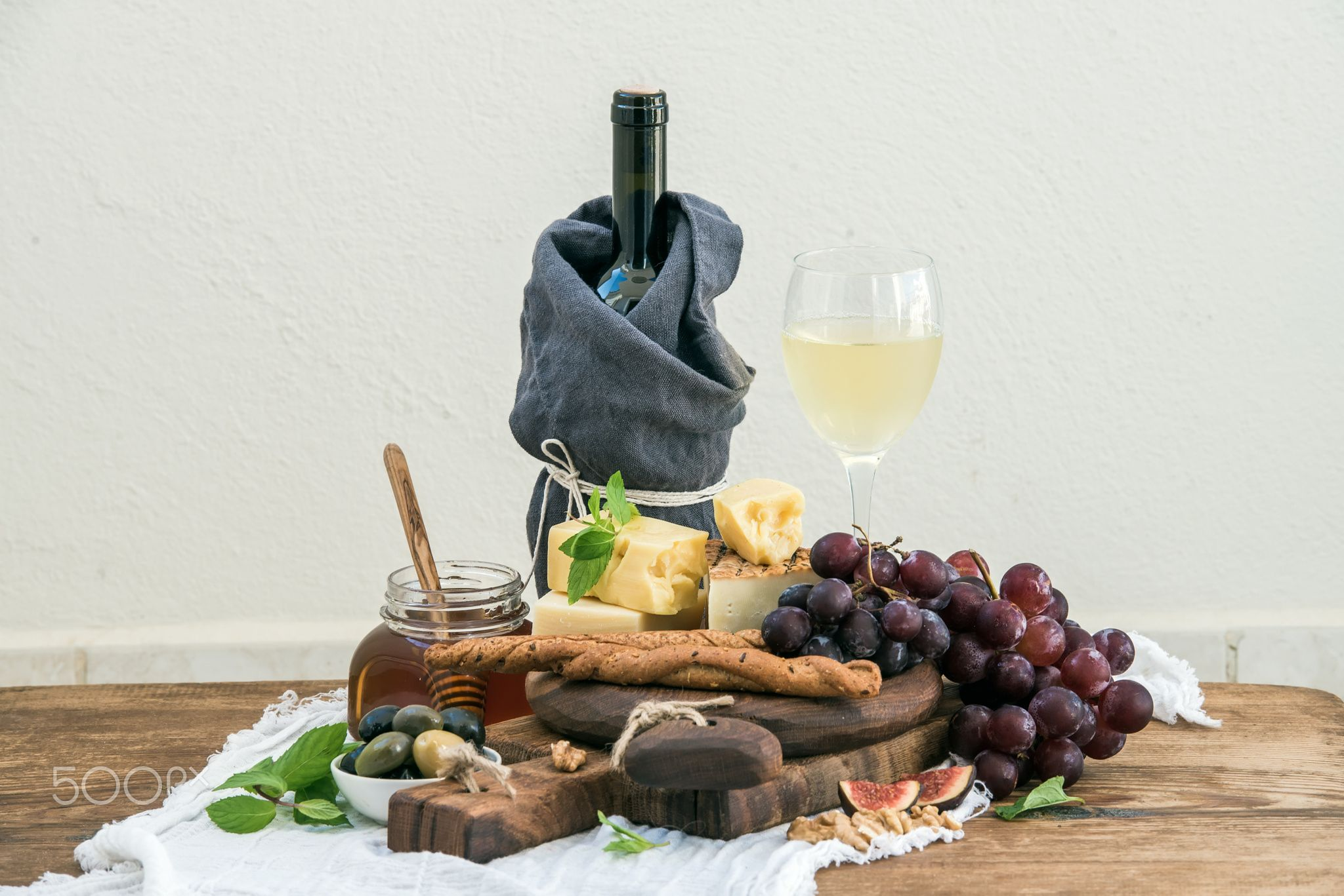 Glass of white wine, cheese board, grapes, fig, strawberries, honey and bread sticks  on rustic wood - Glass of white wine, cheese board, grapes,fig, strawberries, honey and bread sticks  on rustic wooden table, light background, selective focus