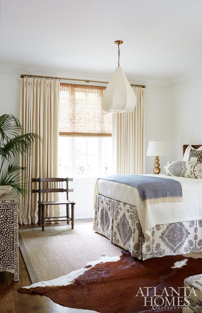 In the guest bedroom, Shayelyn layered finds such as an antique hunting chair from B.D. Jeffries and a pearl-inlay chest of drawers from Bungalow Classic. She commissioned the silk light fixture based on a design she had seen in Morocco. Drapery is custom