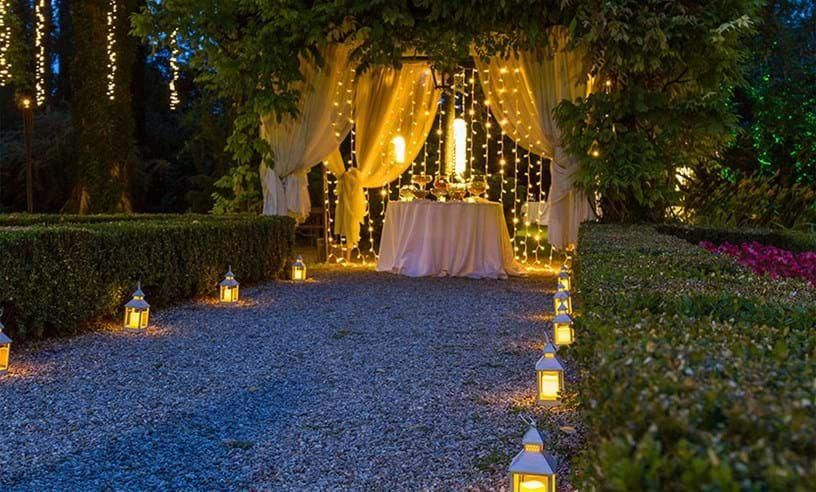 Photo of Illuminated driveway with bright lanterns and curtain of lights for wedding #weddin …
