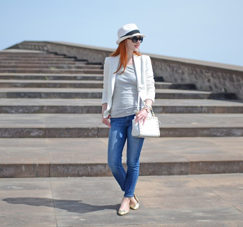 casual spring look: jeans, white blazer, grey t-shirt and hat