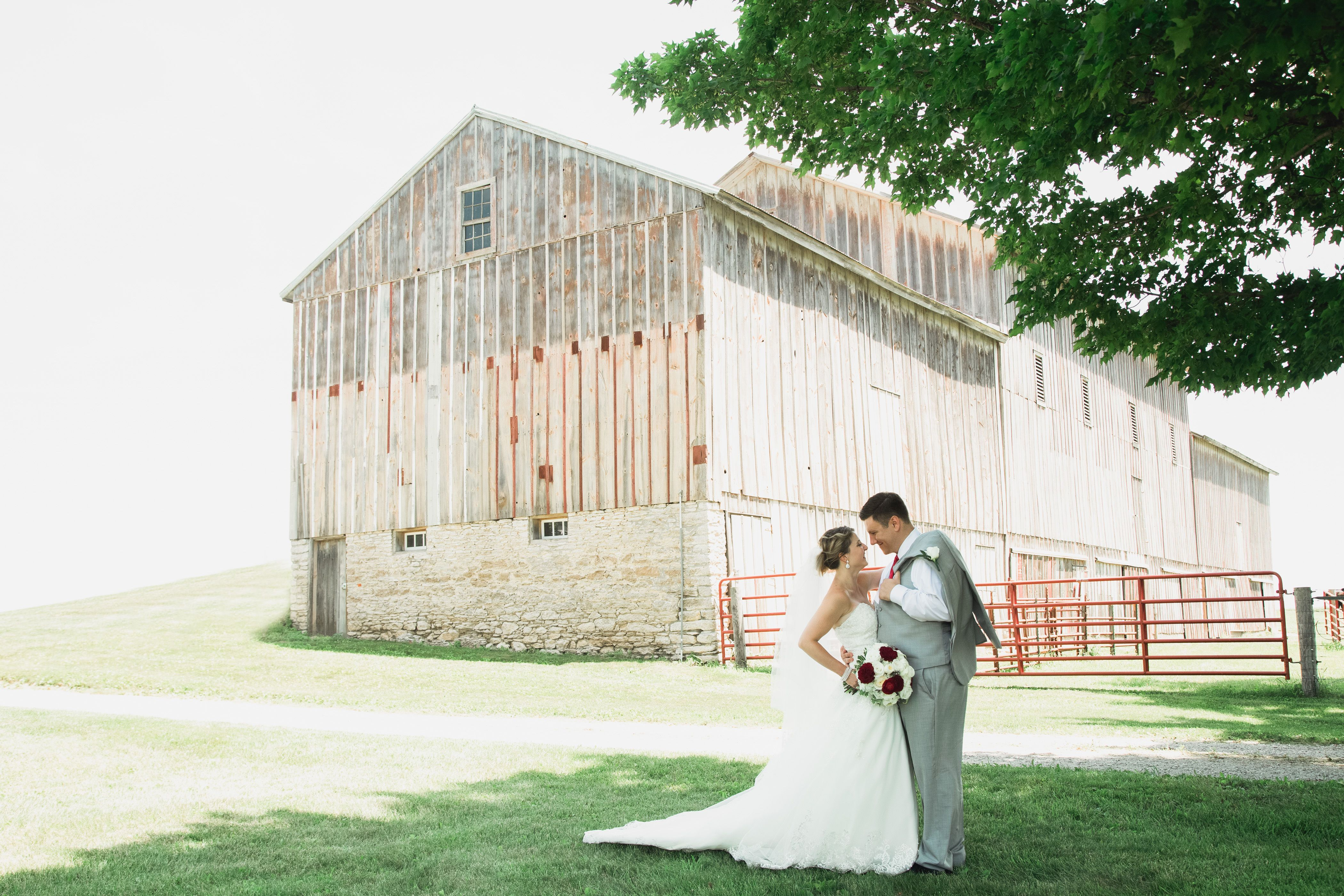 Bride and groom in front of a rustic barn near Solon, Iowa