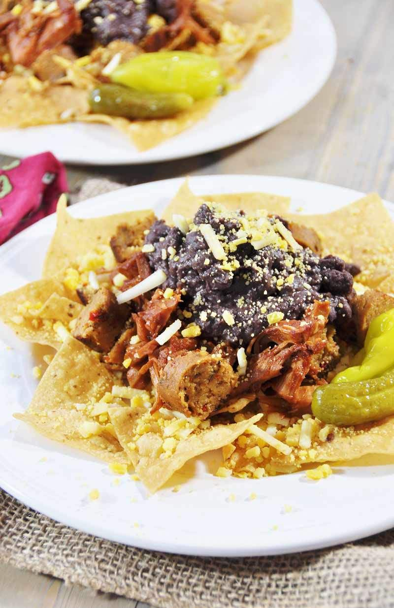 """Vegan """"Gut Pak,"""" Inspired by Fixer Upper and Vitek's! This recipe is like a big plate of nachos, with Field Roast Italian sausage, Upton's BBQ jackfruit, Better Bean Cuban black beans, Go Veggie Mexican shreds, corn chips, and a dill pickle on the side. Quick, easy, and delicious! www.veganosity.com #fixerupper #FieldRoast #Upton's #GoVeggie, #BetterBean"""