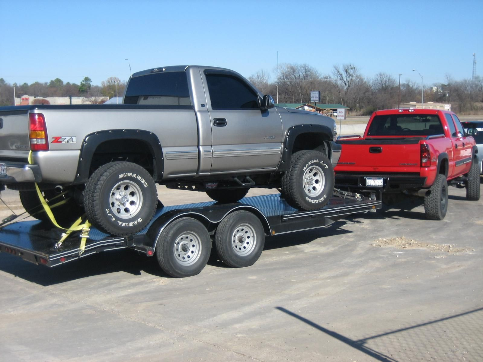 Silver grey lifted gmc truck being towed by a red gmc truck