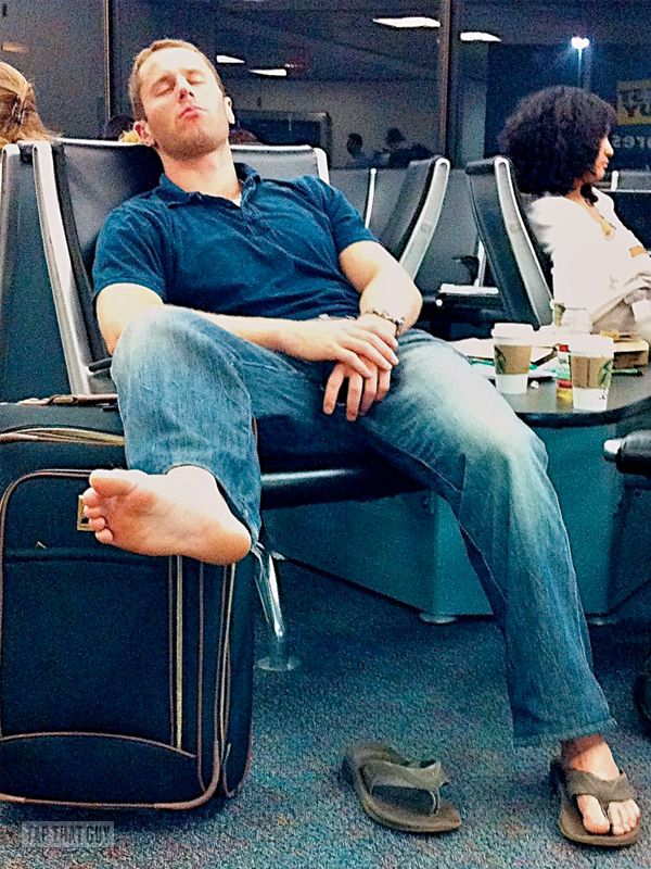 Hot man with hot feet napping at the airport