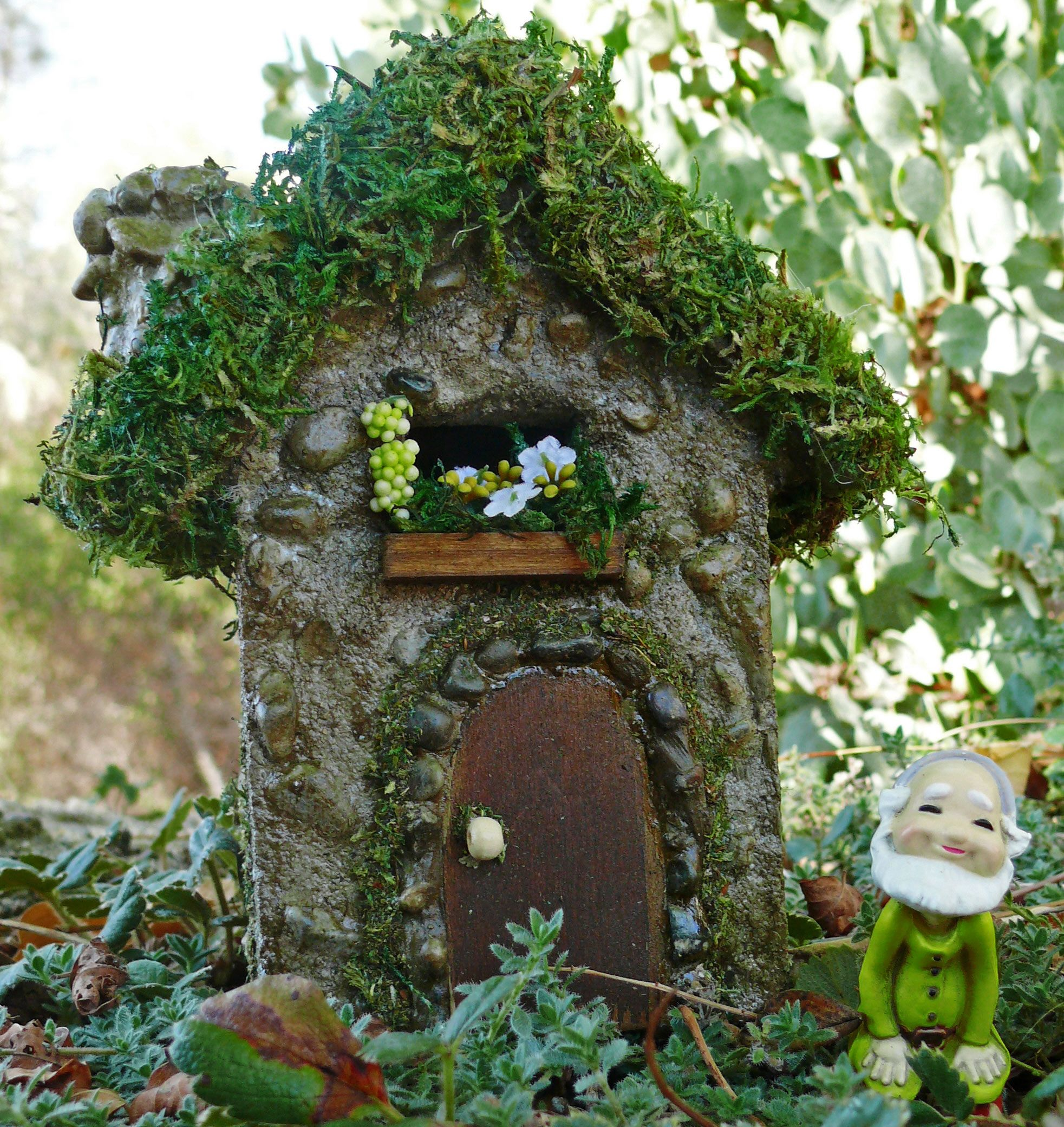 A sunshine infused miniature fairy house with tiny yellow flowers to ...