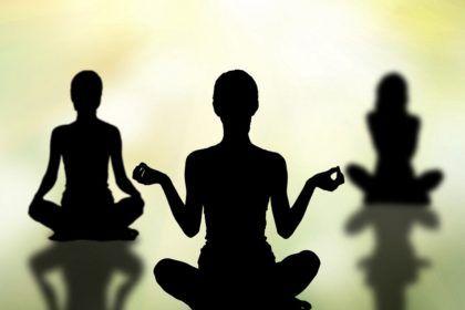 silhouettes of women practicing yoga lotus pose  negative