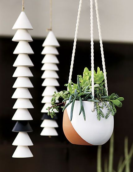 White hand-applied glaze criss-crosses raw terracotta round leaving an earthy swoosh of clay exposed. Suspends plants from a trio of white ropes—-perfect indoors and out.