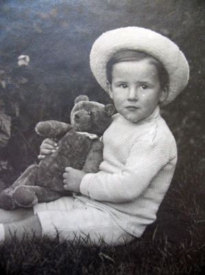 Cute boy holding his Teddy bear, circa 1920.
