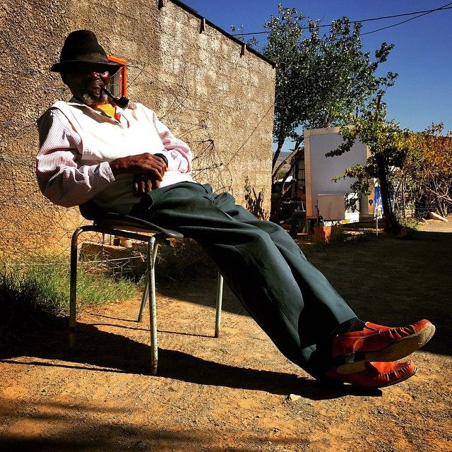 """An old man known as Mtshuleni smokes his pipe whilst basking in the sun in Cradock, Eastern Cape."""""""