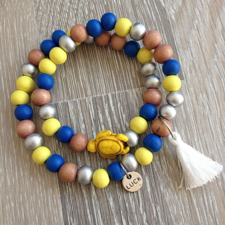 """Wikkelarmband van 8mm roos, lemon yellow, koningsblauw en zilver hout, met gele howliet schildpad, metalen plaatje """"Luck"""" en een wit kwastje. Van JuudsBoetiek, €8,00. Te bestellen op www.juudsboetiek.nl."""