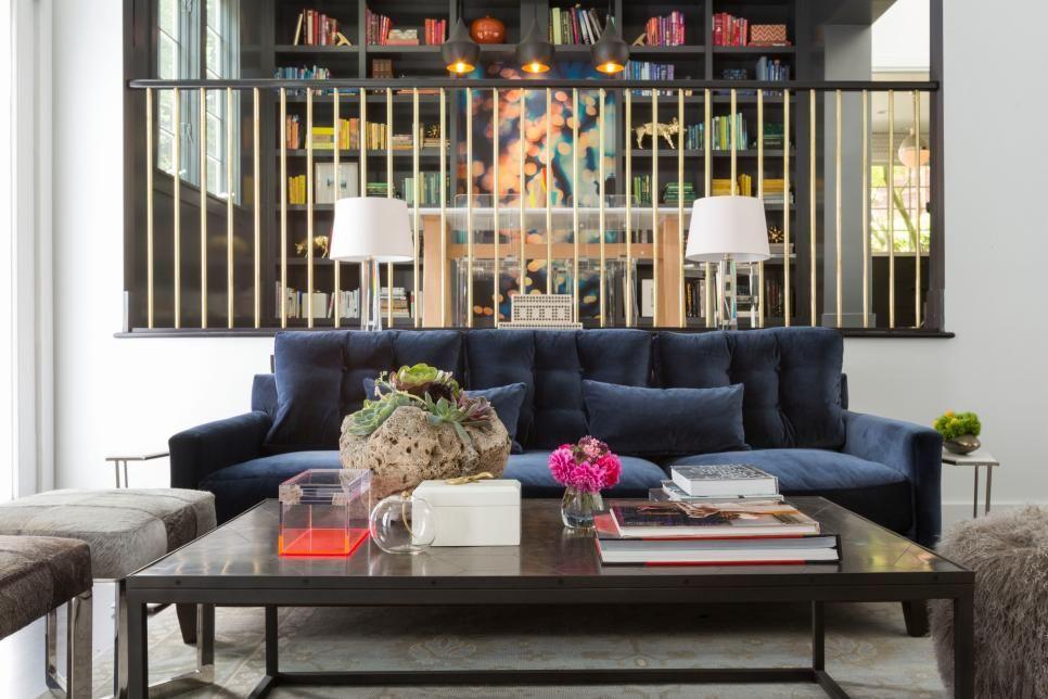 An elegant black and gold railing separates this sunken living room