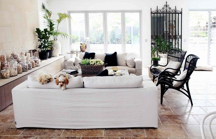 Love this simple space with stone floors, black rattan chairs, white slip covered sofas, side storage. Shells in glass jars. Black, white decor. hannah blackmore 5