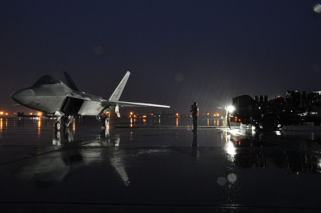 Airmen perform a hot pit refuel with an F-22. Hot pit refueling is a procedure performed in order to rapidly refuel the aircraft and allow it to complete a second sortie in a short amount of time.