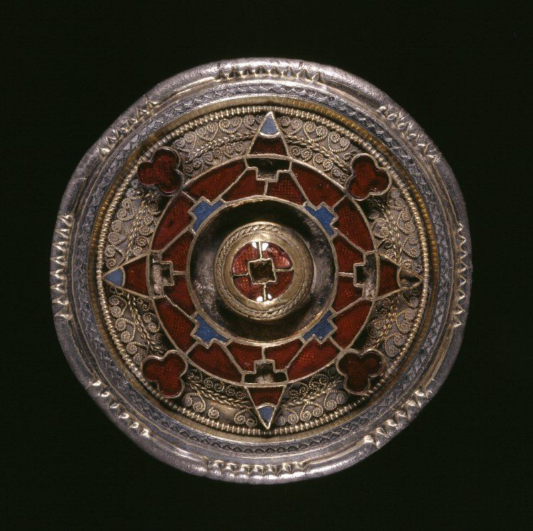 6thC-7thC Disc brooch made of silver-gilt with centre cloisonné garnets and a filigree collar. There are empty and cloisonné zones; triangles, trefoils, scrolls and filigree around edge.