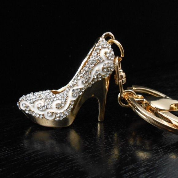 ⭐️Silver Stiletto Purse Charm/Keychain ⭐️ Fashion silver stiletto high heel shoe keychain. Beautifully designed with gold tone metal, and embellished with white enamel, detailed with sparkling silver rhinestone bling. Includes a key ring and a secure lobster clasp, perfect for use as a keychain or purse charm accessory.  Features Clasp: Lobster Clasp Chain Metal: Zinc Alloy Stone: Rhinestone Crystal Measurements: Charm: 1.5 in. x 1.5 in. Chain: 2.5 in. x 1.25 in. Total Measurements: 4 in. x…