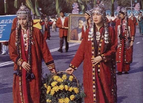 Turkmen women with red robes and head dresses.