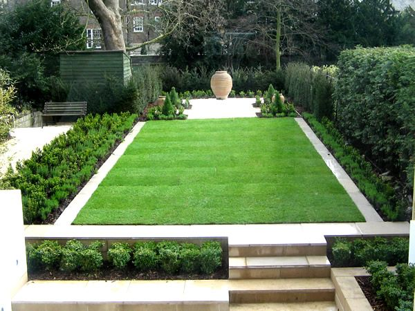 formal contemporary green garden with perfect lawn edged in natural pale stone