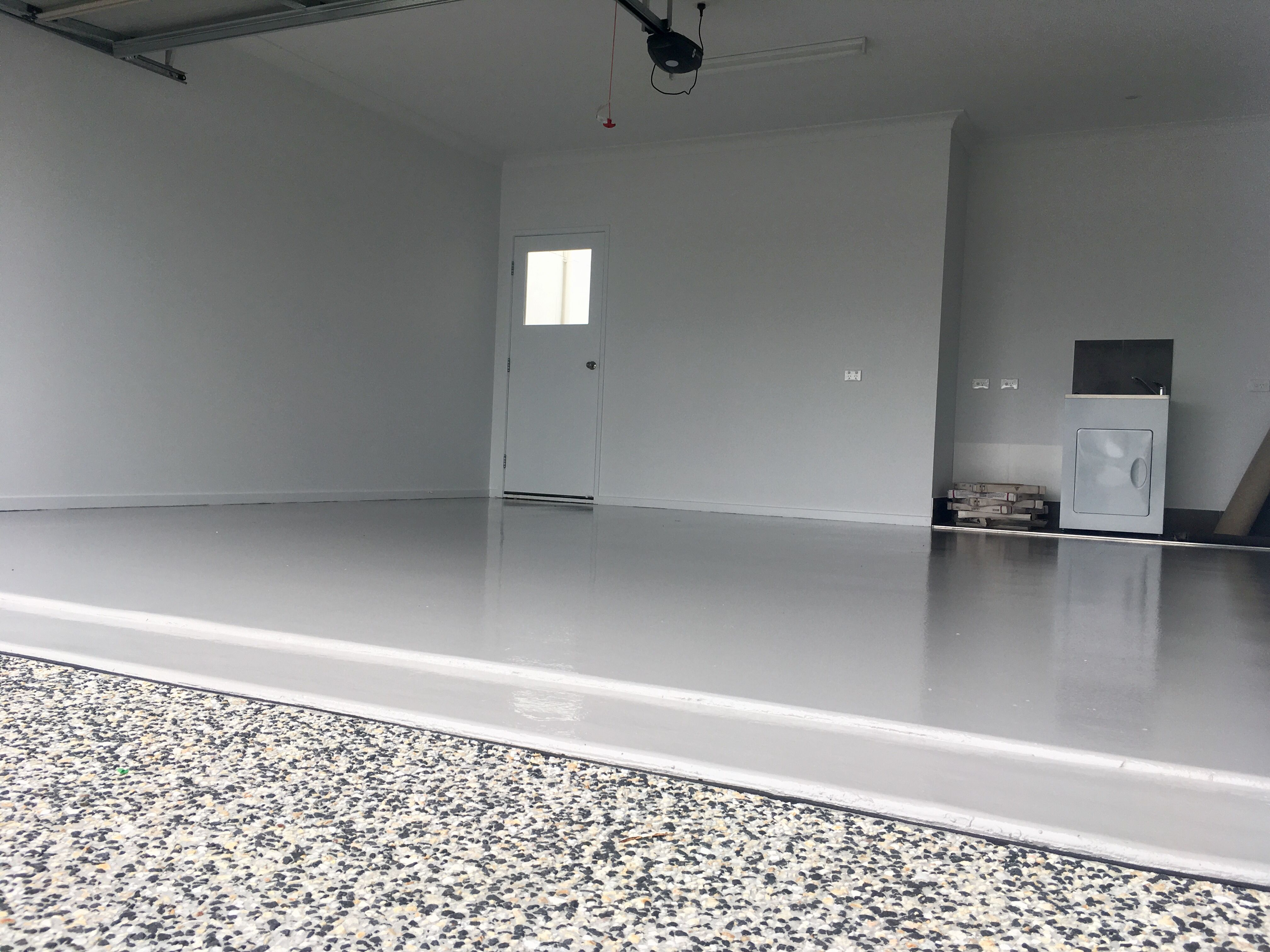 A plain coat epoxy floor installation in a double garage