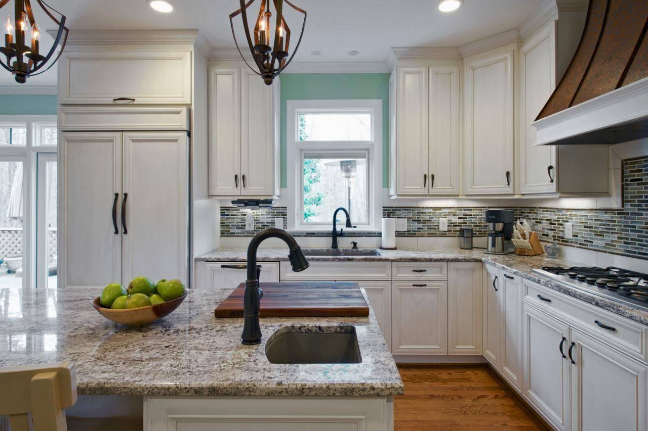 This beautiful, bright kitchen features ample white cabinetry to ...
