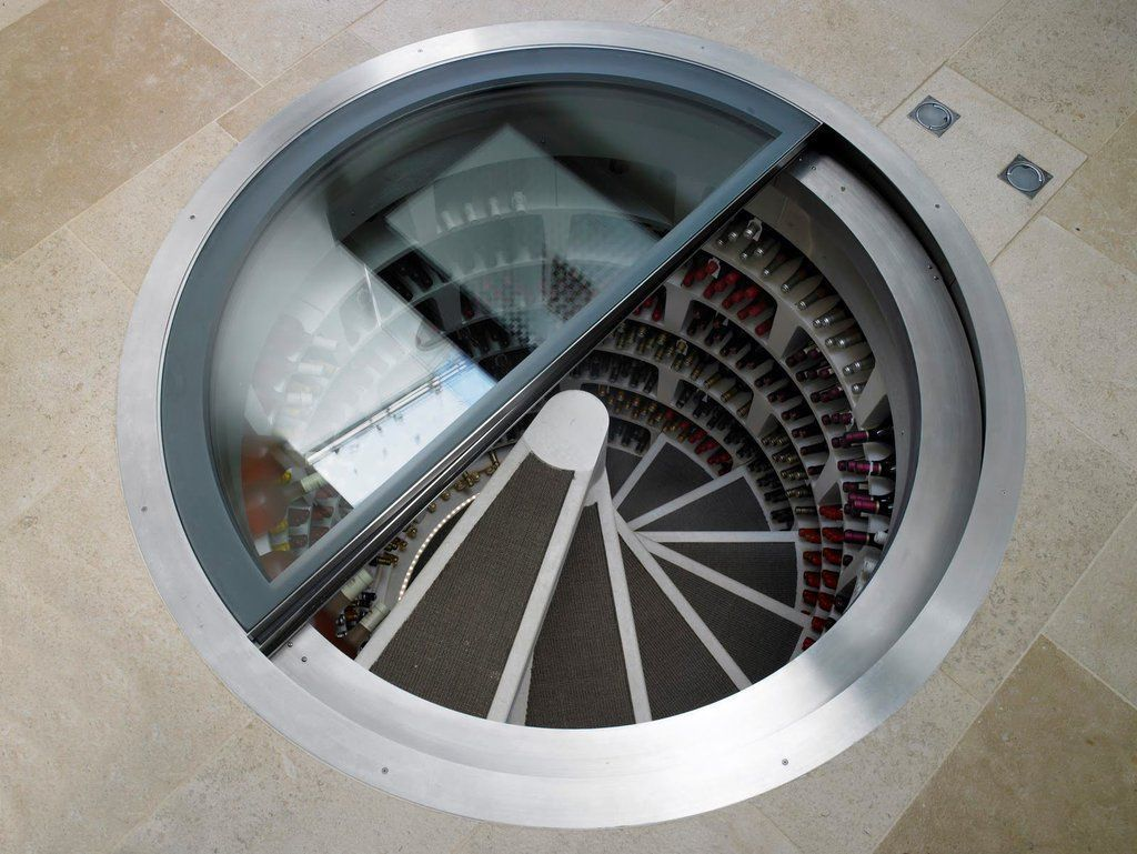 cool underground spiral staircase goes down to stacks of wine