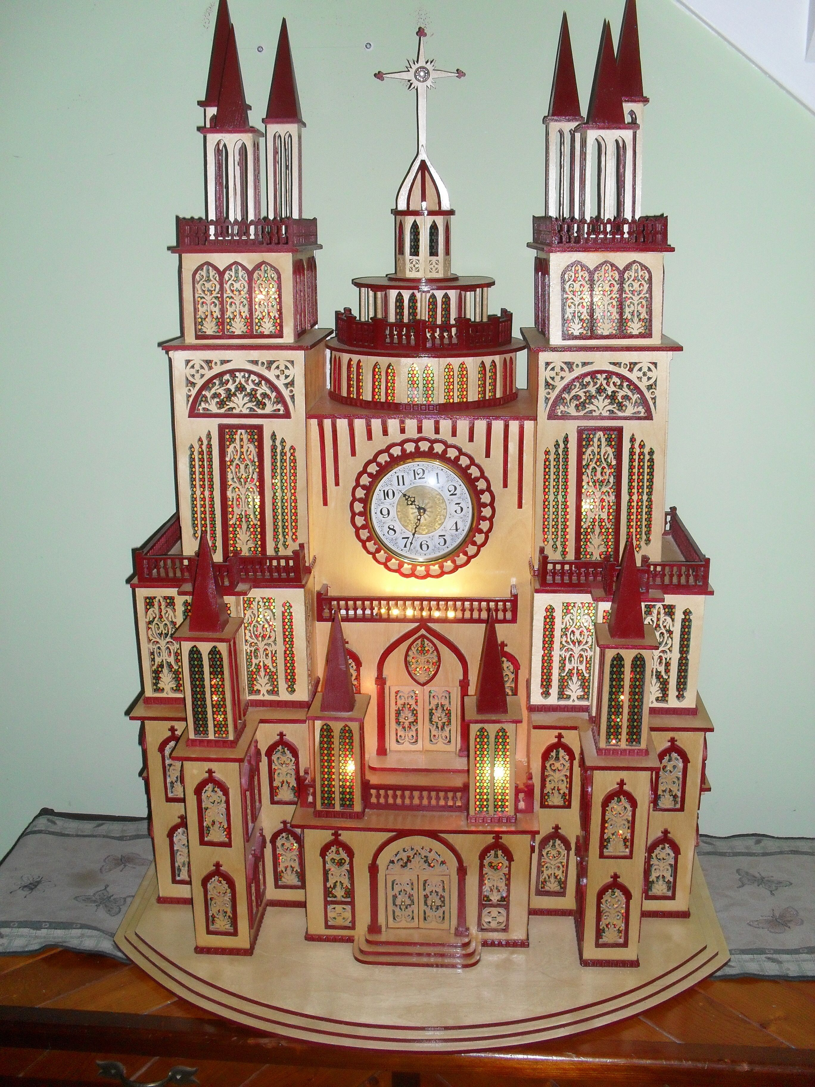 "Shopiere Cathedral Clock     Hand crafted from Baltic Birch, 70 framed windows, 4 doors, and 10 spires with a center rotunda. Over 460 pieces sanded and fitted pieces with 3600 insided cuts hand painted with a satin finish.   Dimentions  44"" high 30 "" wide and 19"" deep"