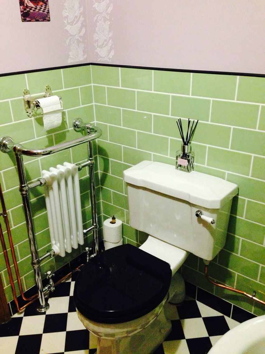 Victorian style toilet and cistern with lovely radiator and brick tiles with black edging