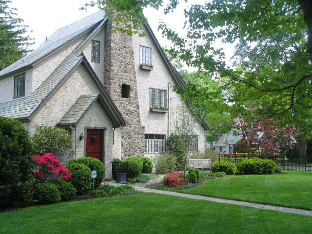 english tudor style home with lush