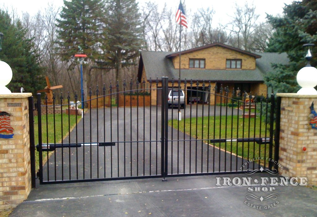 A Wrought Iron Arched Driveway Gate With A Gto Automatic Opener Kit And Complemented By Brick