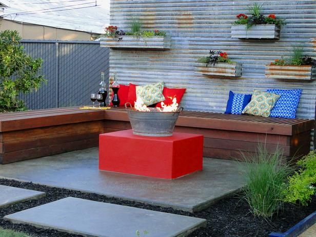 Fire Pit Design Ideas: Corrugated metal is used to build a privacy wall and create a backdrop for a fun gathering space. To make the unusual fire pit, a gas line was run through the recycled metal bucket then filled with lava rock.  From DIYnetwork.com