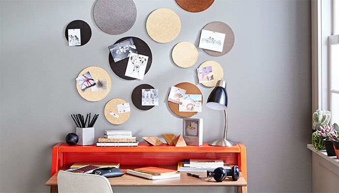 Painted and stained cork rounds on a wall.
