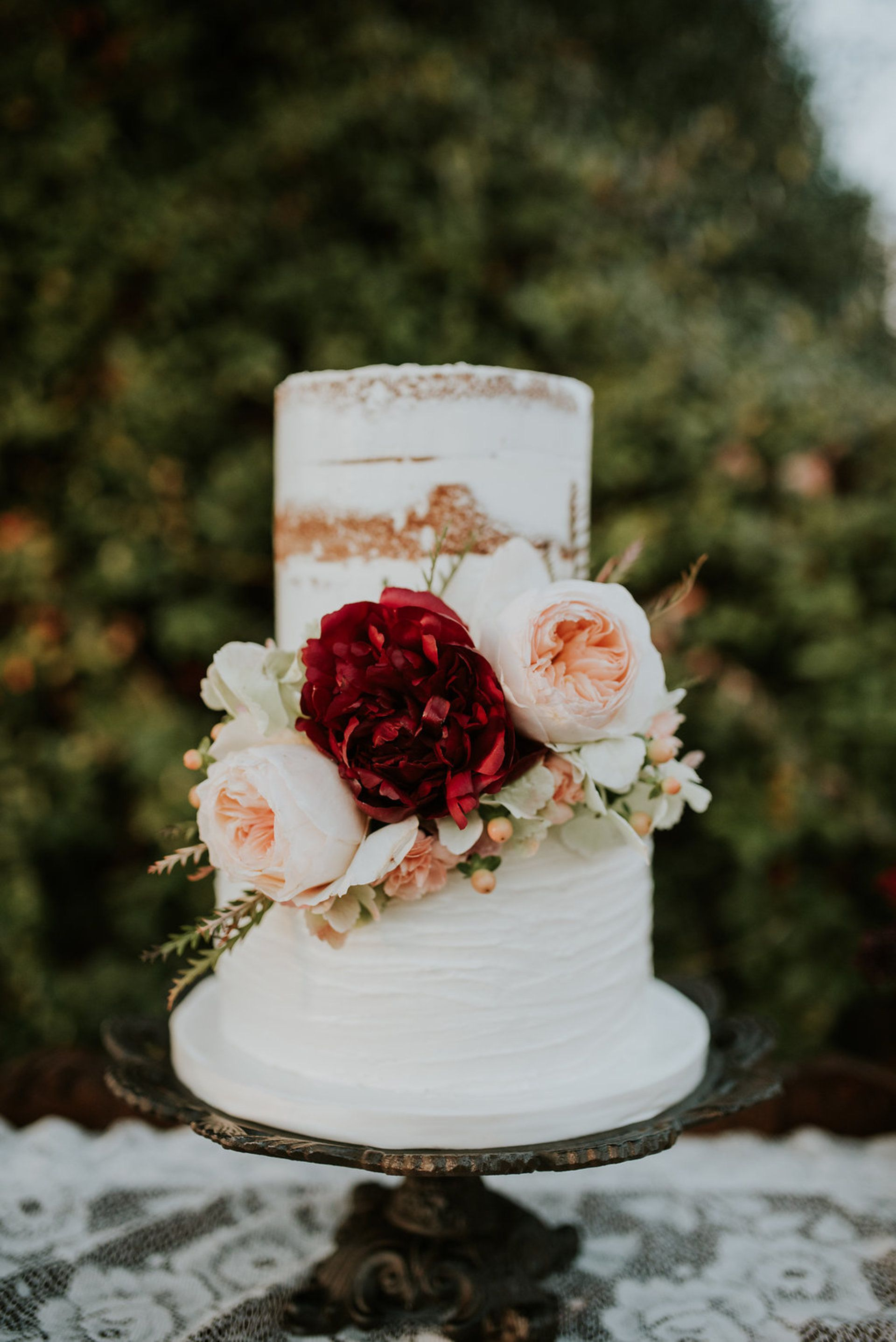 romantic two tier wedding cake peach and dark red florals naked tier thick white frosting moriah elisabeth