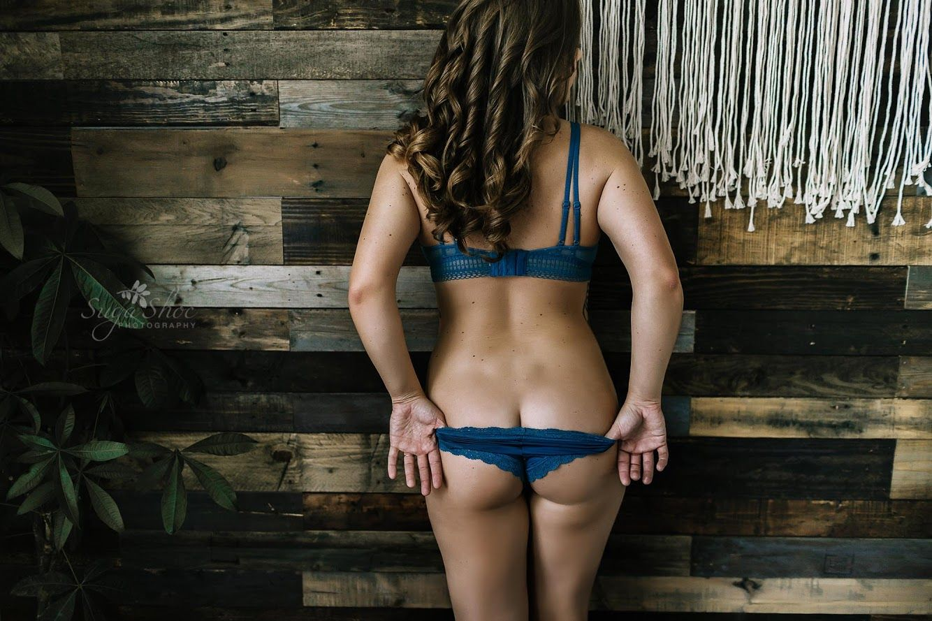 Boudoir pose booty shot woman wearing blue bra and panty and pulling