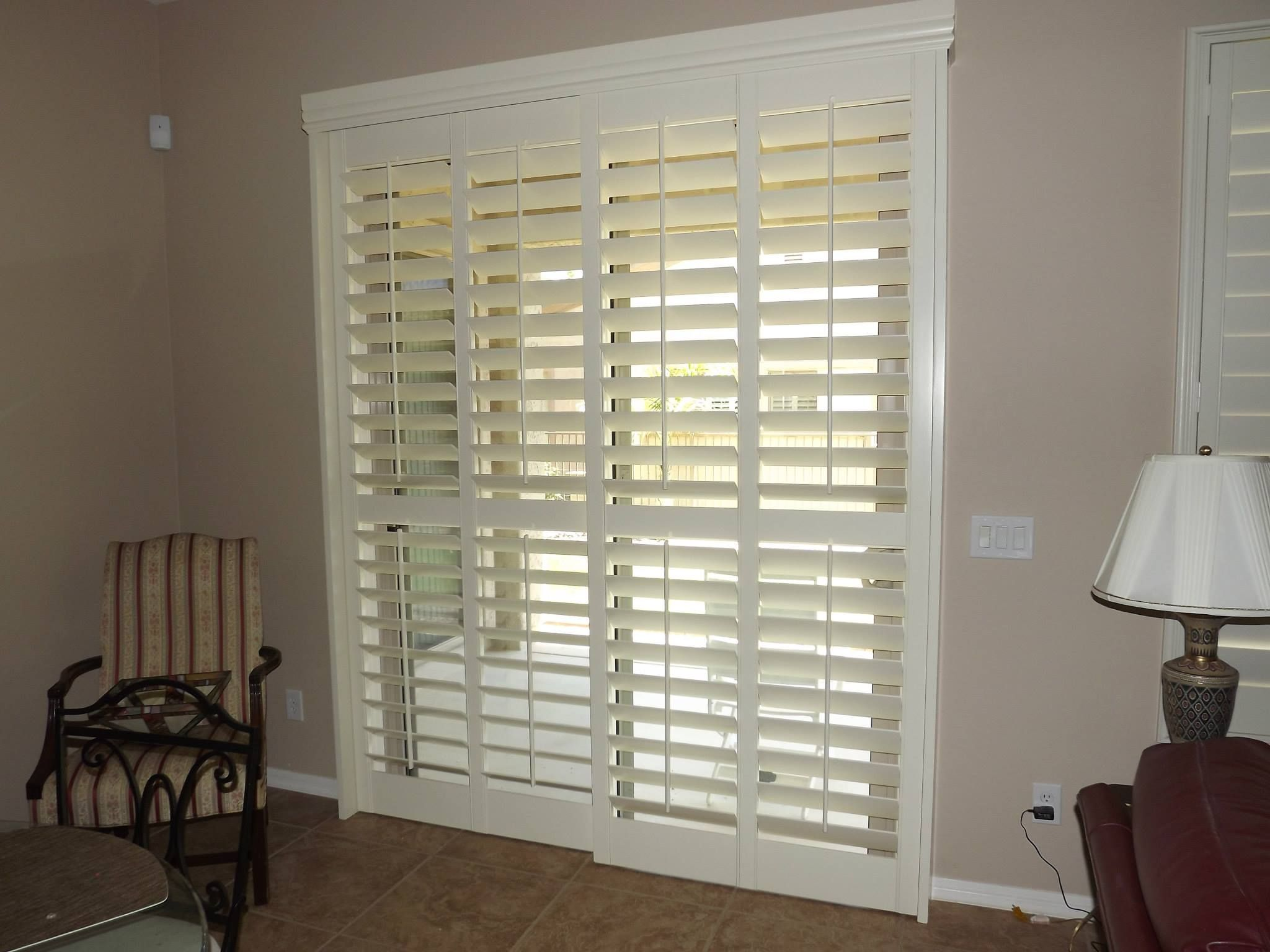 Sliding glass door with the plantation shutters closed but the louvers are all opened