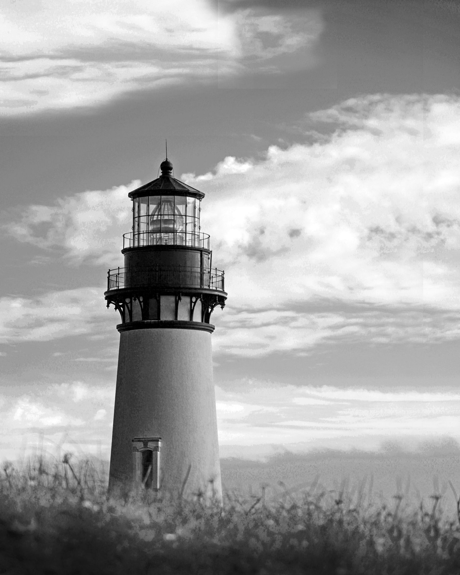 Black and white photography of an oregon lighthouse on a cloudy day