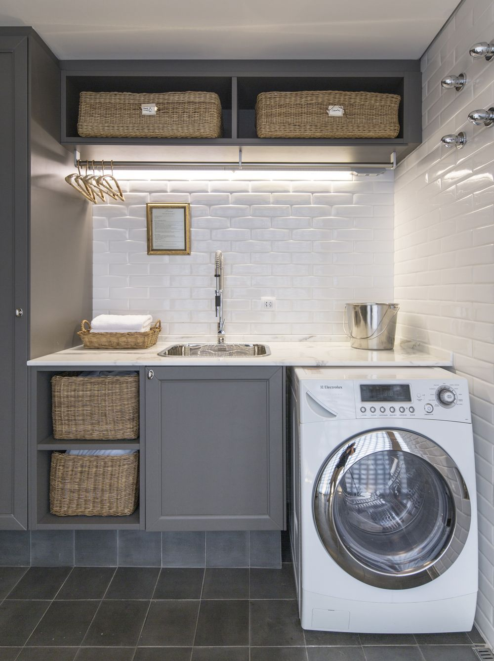 This Laundry Room With Gray Cabinets White Subway Tiles And Brass