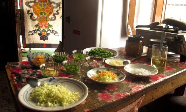 """Erstmal Händewaschen! Hätte zuvor jemand noch Bedenken in Sachen Sauberkeit gehabt, würden die gleich zu allererst von Lhamo ausgeräumt: In seiner winzigen Wohnküche – zwei Tische, ein Kasten, ein TV-Gerät sind die Ausstattung – unterrichtet er seit achtJahren das Zubereiten von tibetischen Gerichten hier in McLeod Ganj, das auch """"Little Lhasa"""" genannt wird. Wobei, in Lhasa selbst sind Tibet ..."""