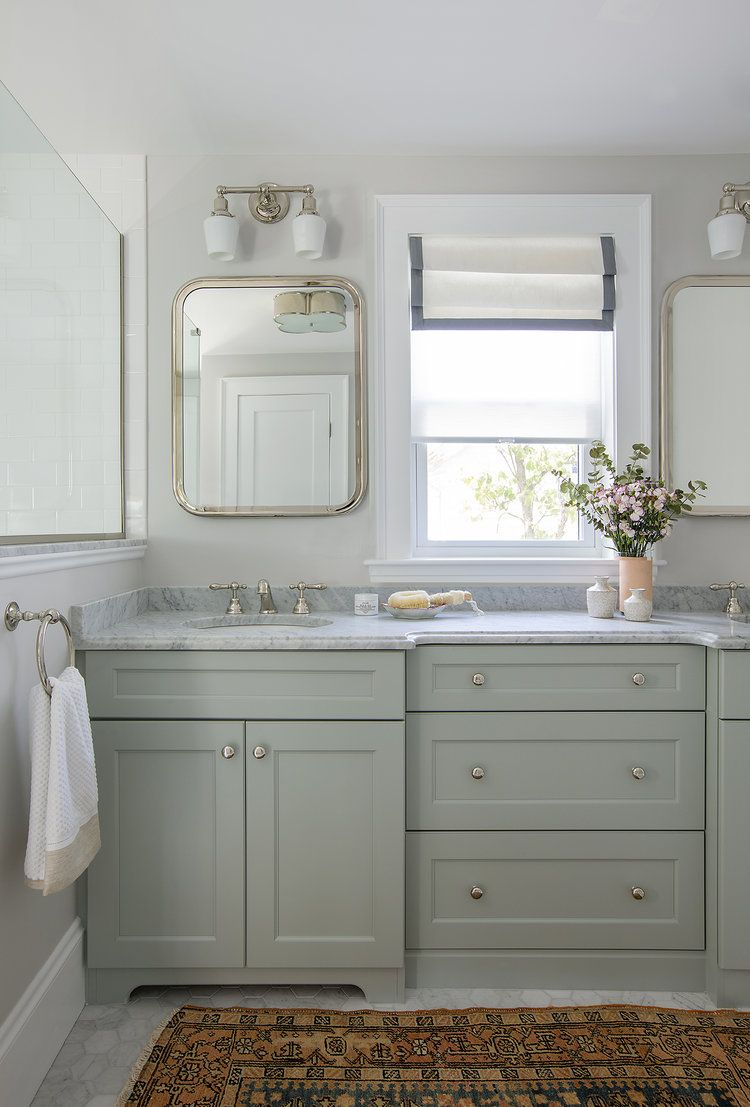 Master Bathroom With Light Green Cabinetry Double Sconces Carrara Countertops And Floors Plus A Vintag Green Vanity Bathroom Vanity Makeover Bathroom Trends