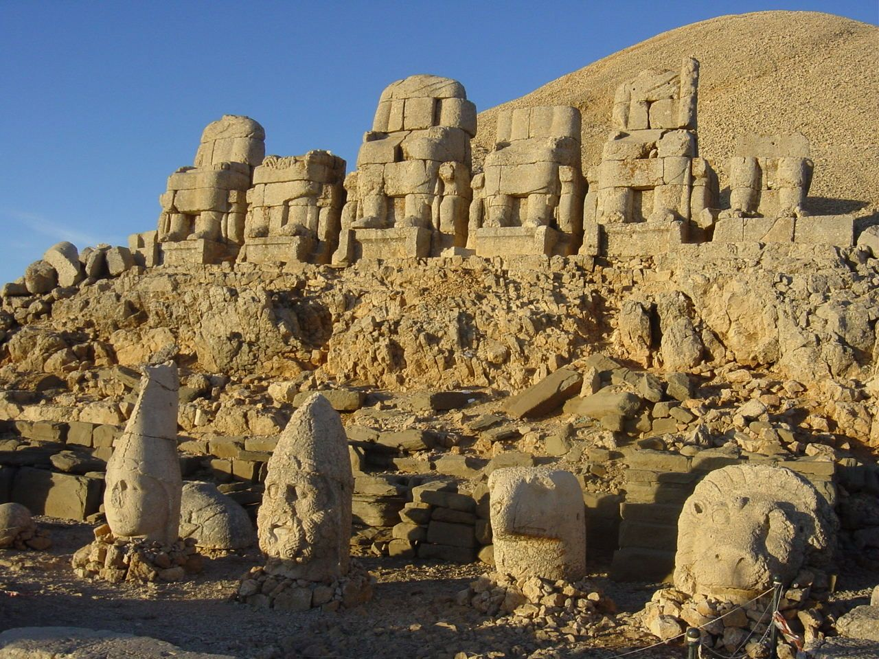 Mount Nemrut (2,134 m high), Turkey. The mountain lies 40 km north of Kahta, near Adıyaman. In 62 BC, King Antiochus I Theos of Commagene built on the mountain top a tomb-sanctuary flanked by huge statues 8–9 m high. These statues were once seated, with names of each god inscribed on them. The heads of the statues have at some stage been removed from their bodies, and they are now scattered throughout the site.