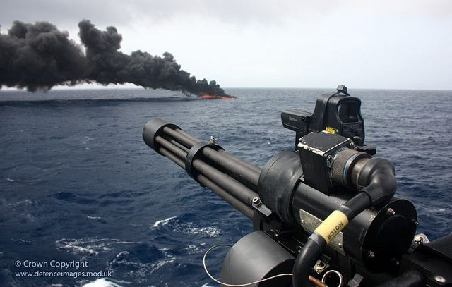 A speedboat burns in the distance after being hit by rounds from the Minigun (foreground) of Type 23 frigate HMS Iron Duke following a drugs seizure and detainment of the crew.
