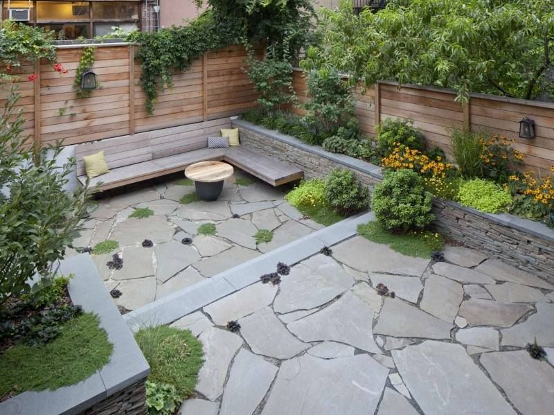 terrasse exterieur avec un sol en pierre et brise vue en bois