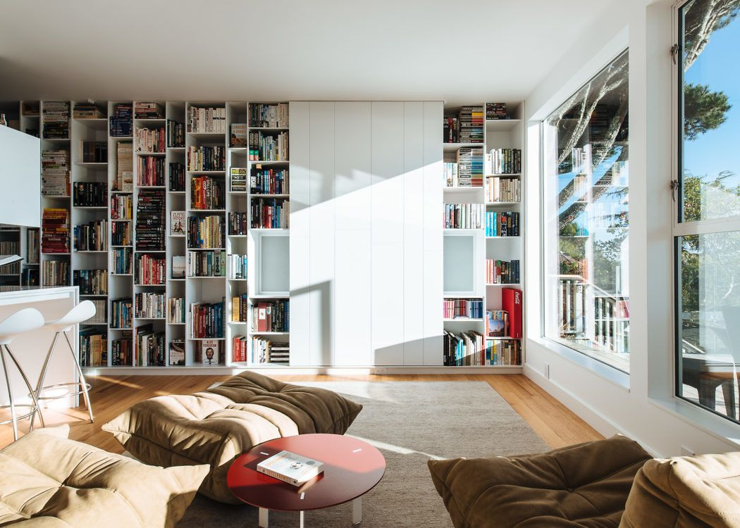 Bright living room with lots of books in white shelves, big window ...