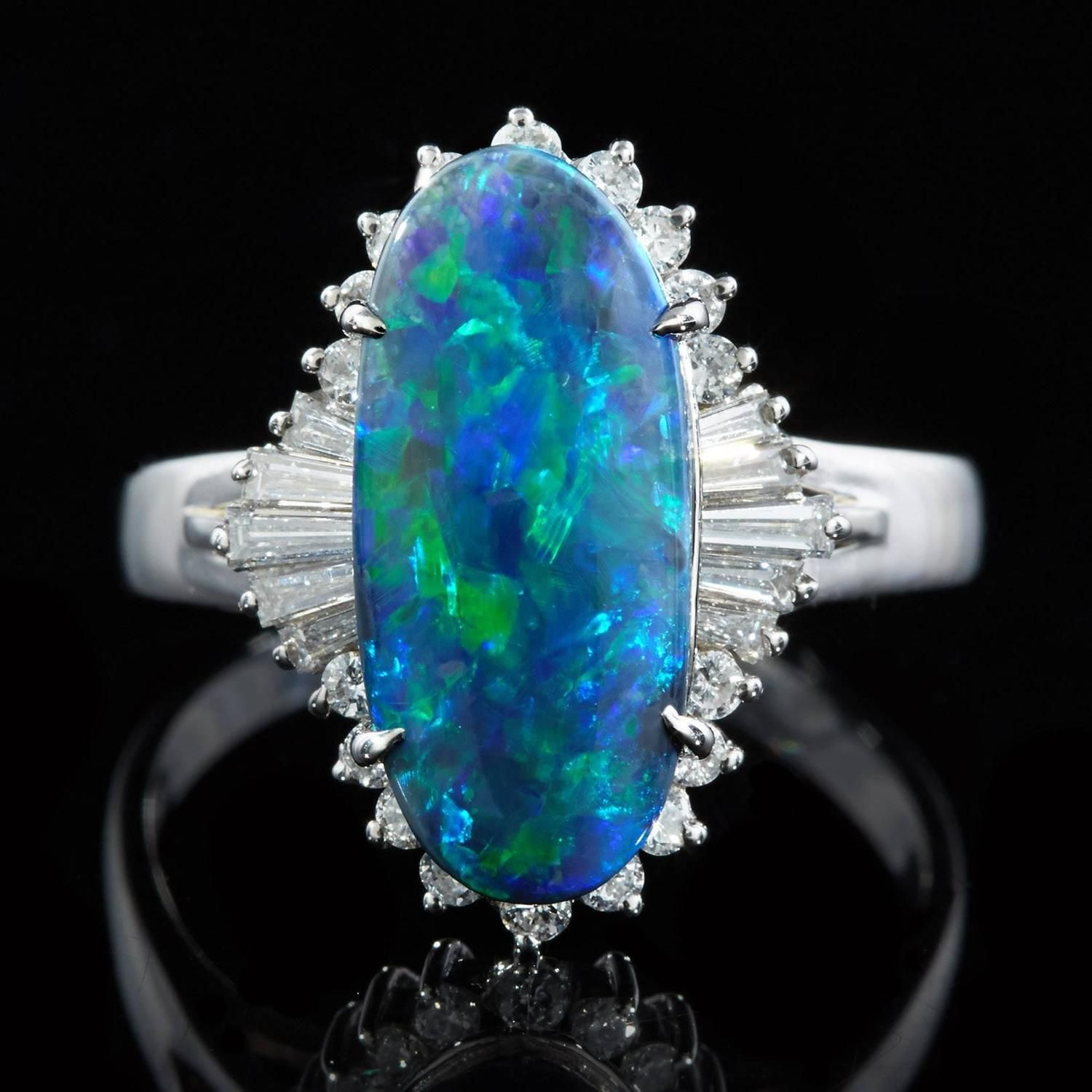 Platinum Ring features a Cabochon Cut Black Opal displaying Blue and Green Play of Color. This opal measures 15.71 x 7.0 mm. A total of 28 round brilliant cut and tapered baguette cut diamonds surrounds the opal with a total of 0.47 carats.