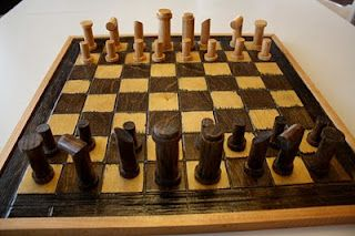 homemade chess set pieces made from wood dowels cut at various angles and glued together.