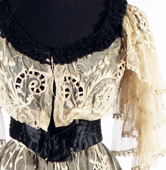 Photo Detail.  1905 Dress by A. Clarke, Cheltenham, England. Black silk and lace. Short bodice of tamboured net with Point de Gaze-style raised flowers over black satin. Sleeves of net frills and wide satin waistband with diamanté button detail. Gored and flared skirt has gathered hem frill. Black silk underskirt. Bonham's.